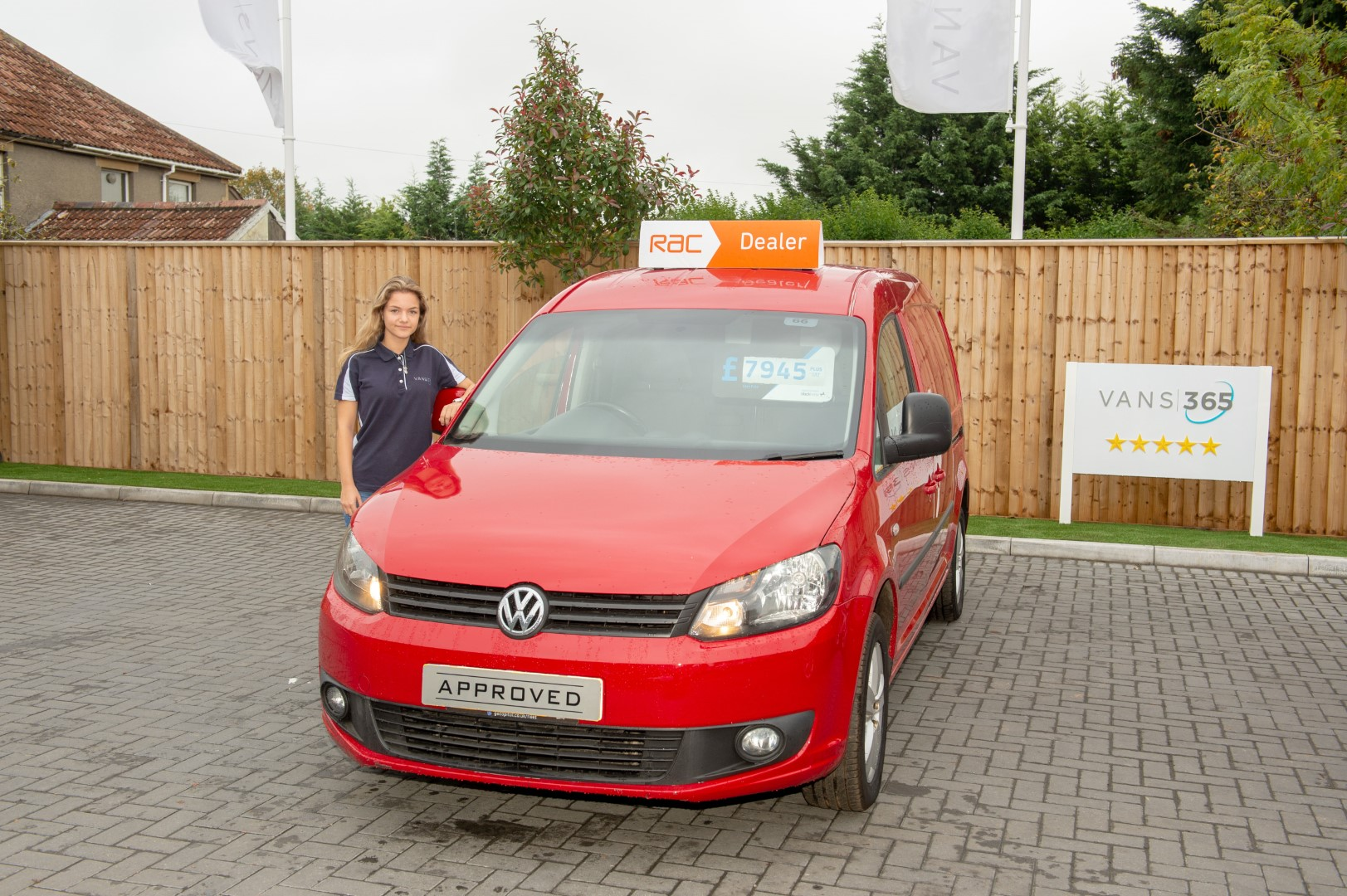 Member of the vans 365 team stood next to a red VW Caddy for sales with a RAC warranty
